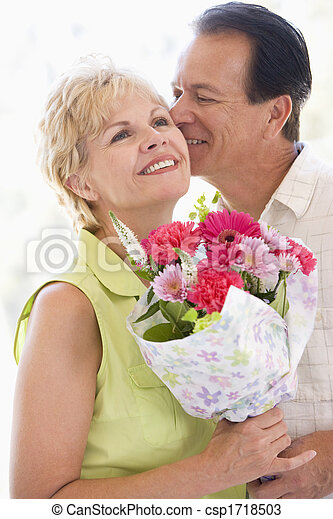 Husband and wife holding flowers kissing and smiling - csp1718503