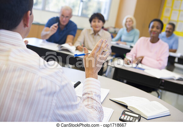 Teacher in class lecturing adult students (selective focus) - csp1718667