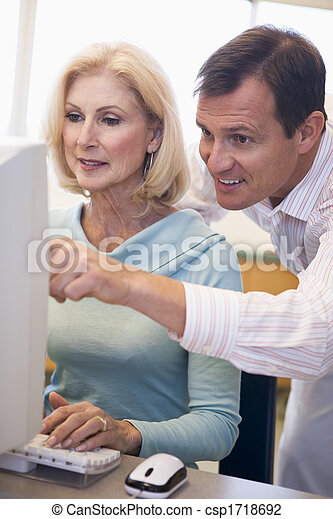 Man and woman at computer typing and pointing (high key) - csp1718692