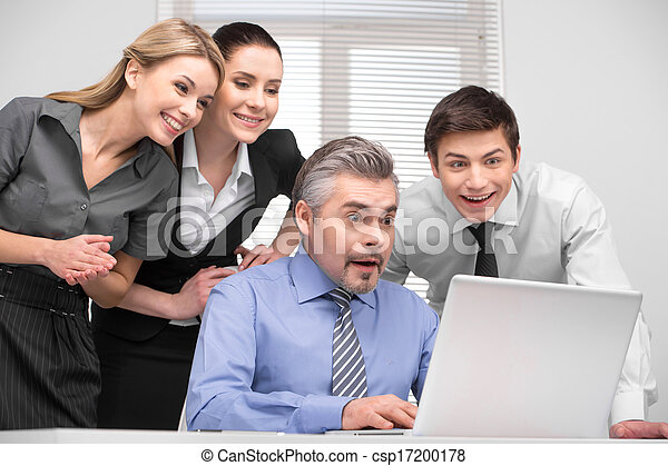 Surprised business team looking on laptop with laughing. Having fun at working place. - csp17200178
