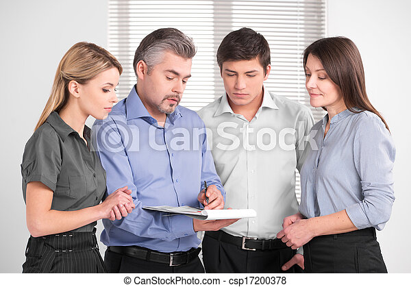 Handsome adult business man showing something on documents. Standing together in bright modern office  - csp17200378