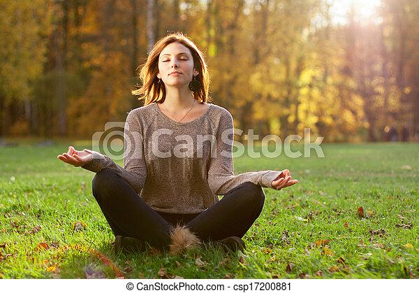 Beautiful young girl meditating in autumn park - csp17200881