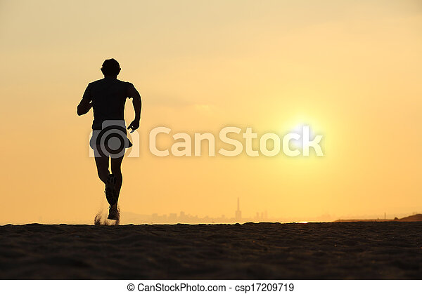Back view of a man running on the beach at sunset - csp17209719