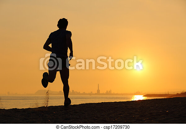 Backlight of a man running on the beach at sunset - csp17209730