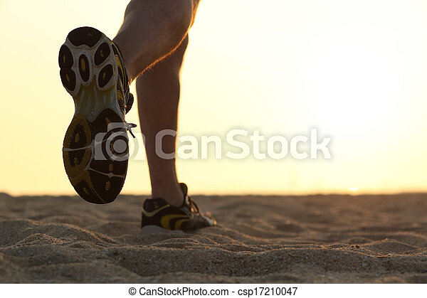 Legs and shoes of a man running at sunset - csp17210047