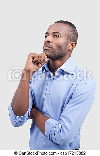 Waiting for inspiration. Thoughtful young man holding hand on chin and looking away while standing isolated on grey background - csp17215882