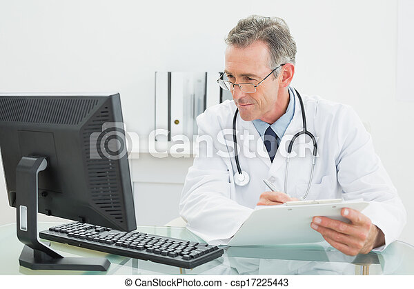 Concentrated male doctor with report looking at computer monitor at desk in medical office - csp17225443