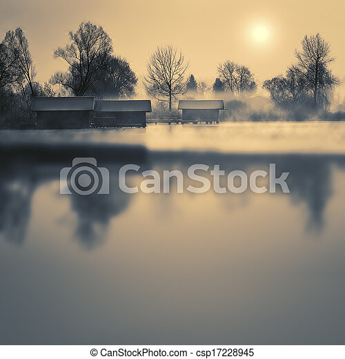 Boathouses on a lake in winter with fog and sun - csp17228945
