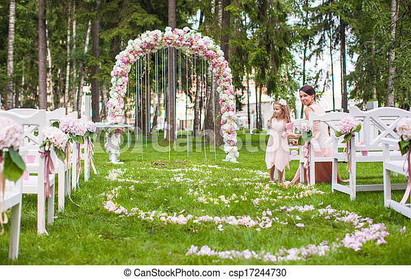 Wedding benches with guests and flower arch for ceremony outdoors - csp17244730