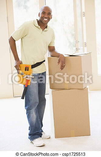 Man wearing tool belt standing by boxes in new home smiling - csp1725513