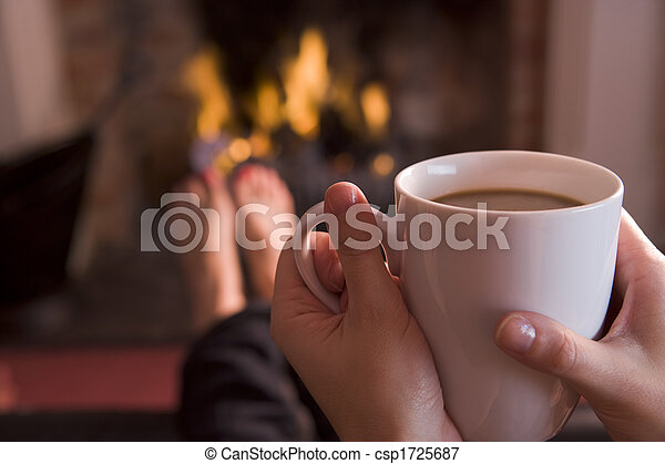 Feet warming at a fireplace with hands holding coffee - csp1725687