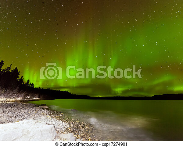 Aurora borealis night sky over Lake Laberge Yukon - csp17274901