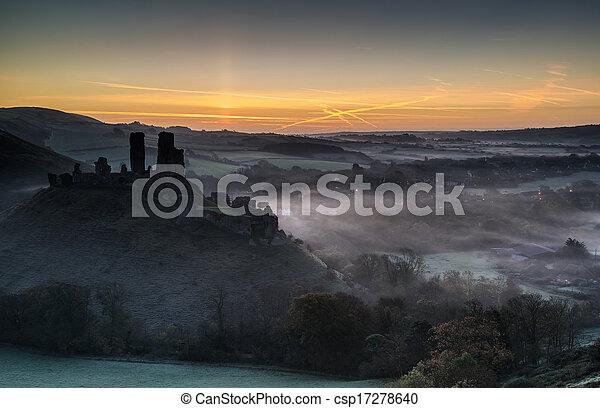 Medieval castle ruins with foggy landscape at sunrise - csp17278640