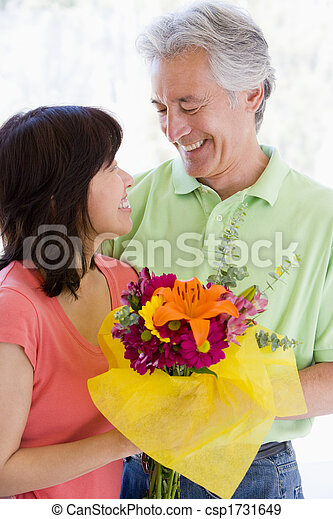 Husband and wife holding flowers and smiling - csp1731649