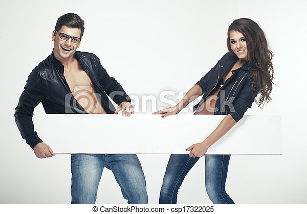 Fashionable happy pretty couple holding white board - csp17322025