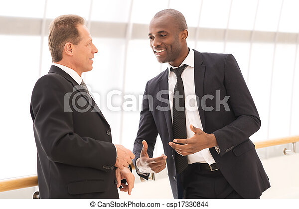 Business communication. Two cheerful business men talking to each other and gesturing - csp17330844