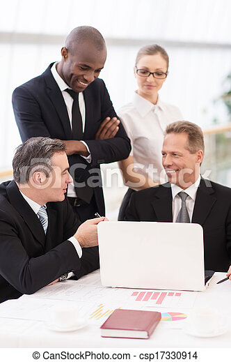 Business team at meeting. Two cheerful mature man in formalwear sitting at the table and communicating while two another people standing close to them  - csp17330914
