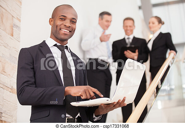 Confident businessman. Cheerful young black man in formalwear standing on staircase and holding a laptop while three people talking on background - csp17331068