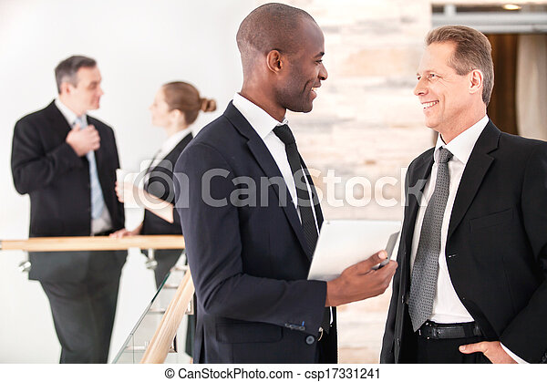 Business communication. Two cheerful business men talking to each other while their colleagues standing on background - csp17331241