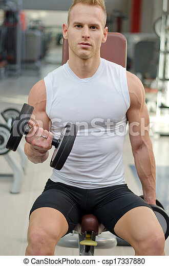 Handsome young man training biceps in gym - csp17337880