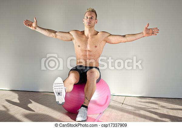 Shirtless young man balancing on fitness ball - csp17337909