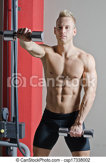Muscular shirtless young man working out in gym with dumbbells - csp17338002