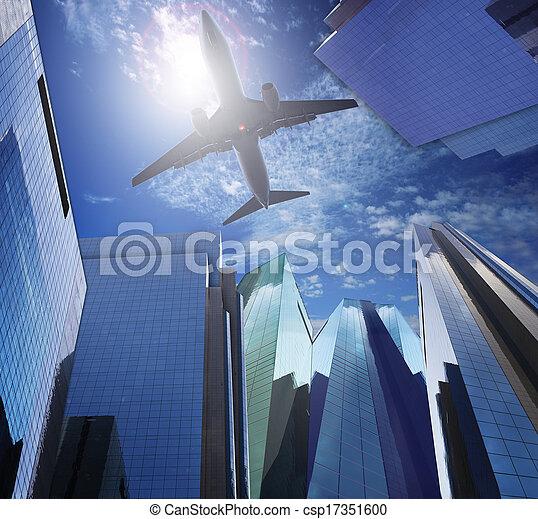 passenger plane flying ove rmodern office building against blue  - csp17351600