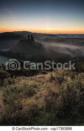 Medieval castle ruins with foggy landscape at sunrise - csp17363886