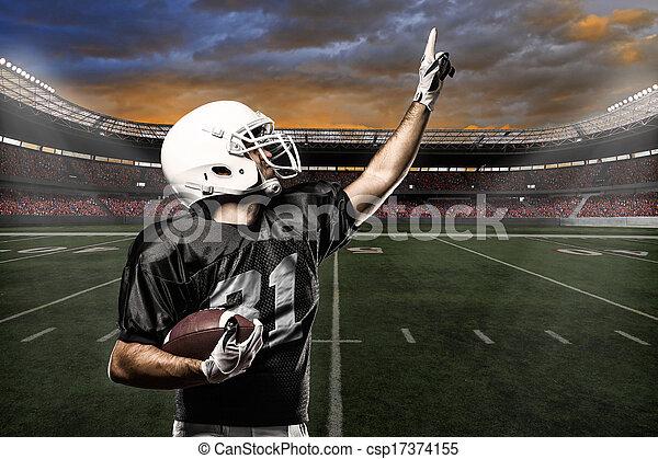 Football Player with a black uniform celebrating on a stadium.