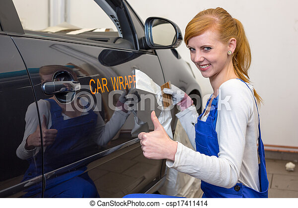 Car branding specialist puts logo with car wrapping film on automobile - csp17411414