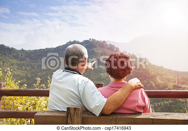 senior couple sitting on the bench looking the nature view - csp17416943