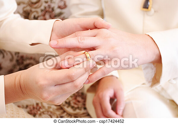 bride putting a wedding ring on groom 's finger, close up - csp17424452