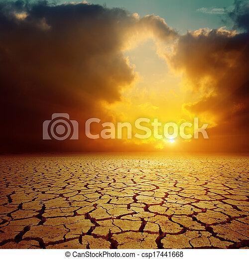 orange cloudy sunset over cracked desert - csp17441668