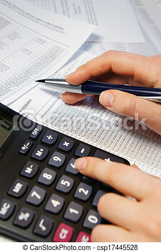 Office table with calculator, pen and accounting document - csp17445528