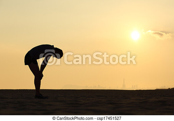 Silhouette of an exhausted sportsman at sunset - csp17451527