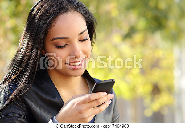 Portrait of a beautiful woman typing on the smart phone in a park - csp17464900