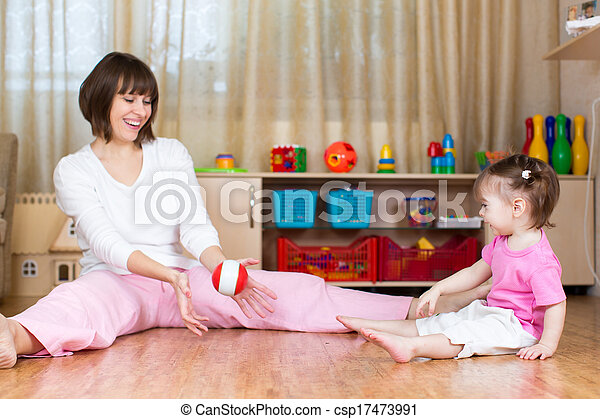 mother and kid play with toy ball indoors - csp17473991