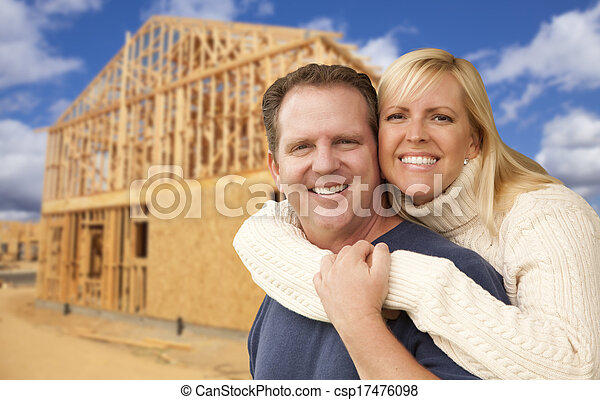 Couple in Front of New Home Construction Framing Site - csp17476098