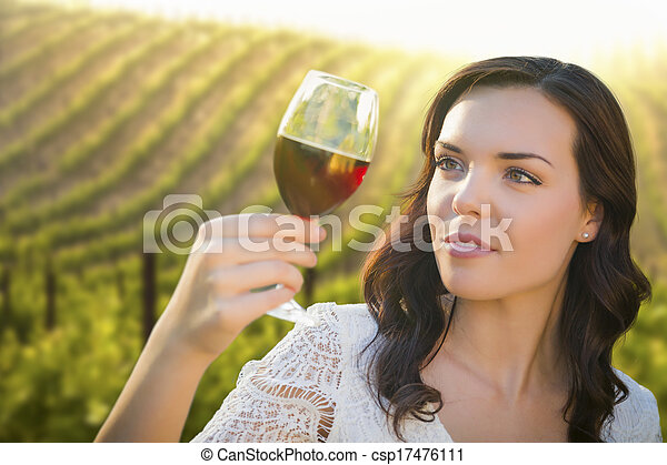 Young Adult Woman Enjoying A Glass of Wine in Vineyard - csp17476111