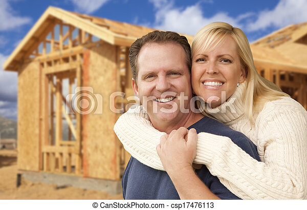Couple in Front of New Home Construction Framing Site - csp17476113