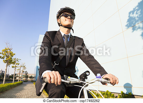businessman riding a bicycle to workplace for protecting environment - csp17492262