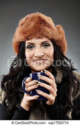 Cheerful woman holding a mug of hot tea