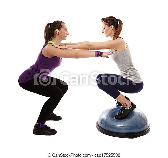 Studio shot of woman doing squats on a bosu ball, helped by the personal trainer, isolated over white background - csp17525502