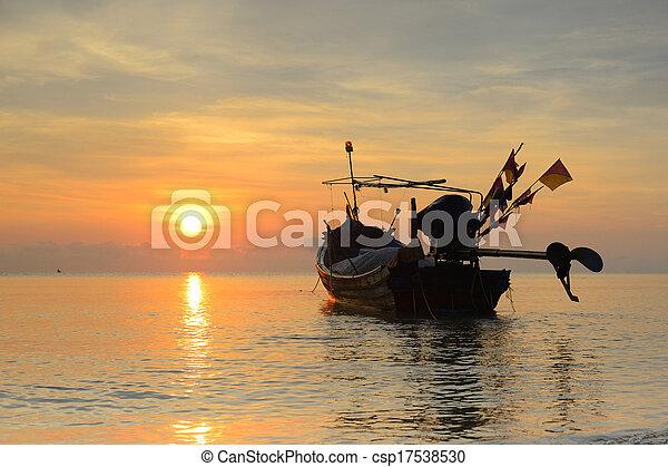 fishing boat with sunrise backdrop. - csp17538530