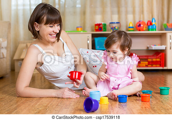 kid girl and mother playing together with cup toys - csp17539118