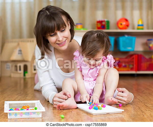 mom and her kid girl play toys in children room - csp17555869