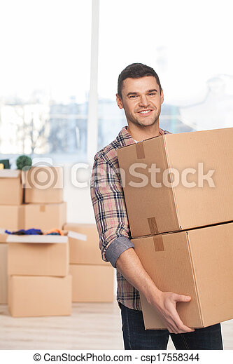 Moving to a new place. Cheerful young man holding a cardboard box and smiling at camera while more carton boxes laying on background - csp17558344