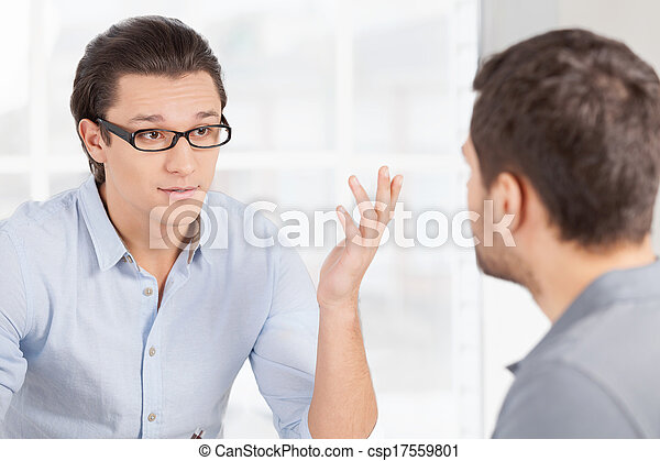 Business communication. Two confident business people in casual wear discussing something and gesturing  - csp17559801