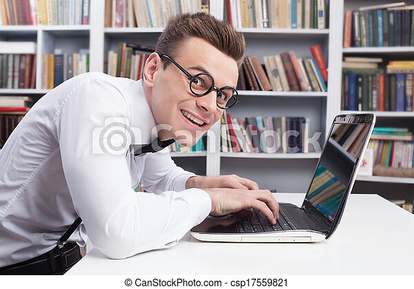 Computer geek. Side view of young nerd man in shirt and bow tie typing something on computer and looking at camera with smile - csp17559821