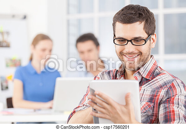 Creative team. Cheerful young man in glasses using digital tablet and smiling while his colleagues working on the background - csp17560201